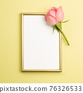 Picture frame with pink rose flower on yellow background. flat lay, top view, copy space 76326533