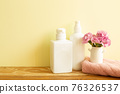 Skin care and spa concept. Bathroom bottles and towel with pink flowers on wooden shelf. yellow background 76326537