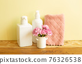 Skin care and spa concept. Bathroom bottles and towel with pink flowers on wooden shelf. yellow background 76326538
