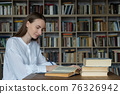 Young woman sitting at table with books and laptop in university library and studying 76326942