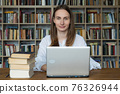 Woman using laptop and learning online. Young woman student study in the library 76326944