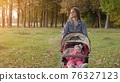 A young mother with a stroller walks in the autumn evening. 76327123