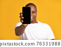 Cheerful middle aged african american male in white t-shirt shows smartphone with blank screen 76331988