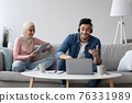 Positive muslim family working online during pandemic 76331989