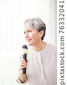 Happy senior woman singing with microphone. 76332041