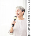 Happy senior woman singing with microphone. 76332043