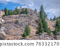 View at rocky mountain slop on cloudy sky background 76332170