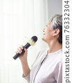 Happy senior asian woman singing with microphone. 76332304