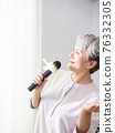 Happy senior asian woman singing with microphone. 76332305