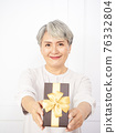Senior asian woman happy smile hold gift box in hands. 76332804