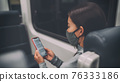 Coronavirus lifestyle bus passenger using mobile phone during commute at night during curfew and lockdown. Woman texting online on contact tracing app while wearing face mask. 76333186