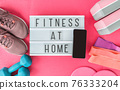 Fitness at home sign with mobile phone on pink yoga mat, running shoes, kettlebell weight and dumbells resistance bands and sliders for pilates online class. Exercise indoors for women. 76333204