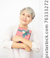 Senior asian woman happy smile hold gift box in hands. 76333272