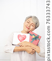 Senior asian woman happy smile hold gift box and greeting card in hands. 76333743
