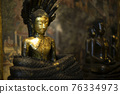 Ancient buddha and snake statue as background 76334973