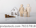 Small model of house with coins and family 76337818