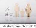 Wooden model of house and family isolated on white background. Close-up 76337819
