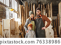 Cheerful parents with kid in craft workshop 76338986
