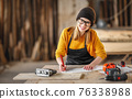 Smiling craftswoman working with l  papers in joinery workshop 76338988
