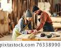 Couple of joiners working with wooden detail in workshop 76338990