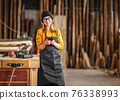 Female joiner using smartphone in workshop 76338993