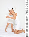 beautiful mother and daughter in white bathrobes and towels 76339631