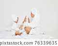 mother and daughter in white bathrobes and towels 76339635