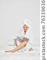 cute woman in white bathrobes read magazines 76339636