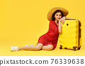 woman with suitcase going traveling on yellow background. 76339638