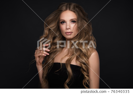 Beautiful blond girl with a perfectly curls hair, and classic make-up. Beauty face and hair. 76340335