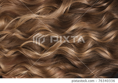 A closeup view of a bunch of shiny curls blond hair 76340336