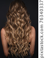 A closeup view of a bunch of shiny curls blond hair 76340337