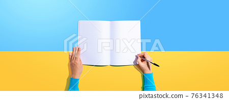Person writing in a notebook 76341348