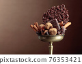 Various chocolates with ingredients in an old brass bowl. 76353421