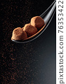 Chocolate candy truffle and flying cocoa powder on a dark background. 76353422