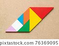 Color tangram puzzle in parallelogram shape on wood background 76369095