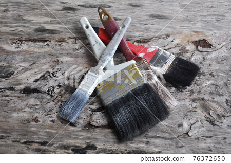 Old paint brush on old wood board. 76372650