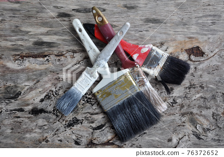 Old paint brush on old wood board. 76372652