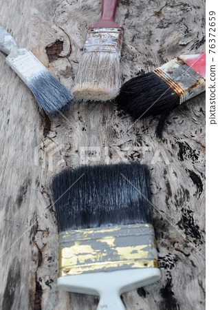 Old paint brush on old wood board. 76372659