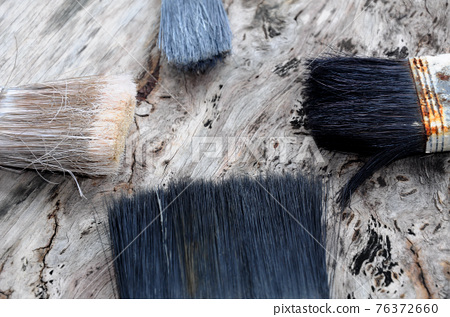 Old paint brush on old wood board. 76372660