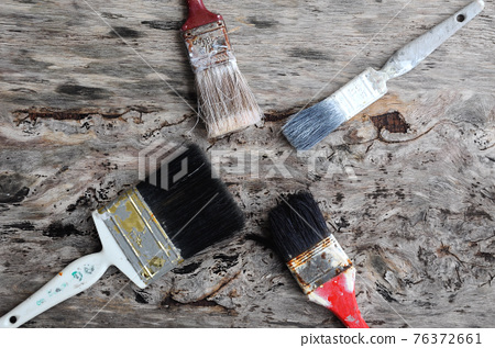 Old paint brush on old wood board. 76372661
