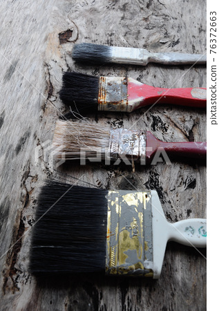 Old paint brush on old wood board. 76372663