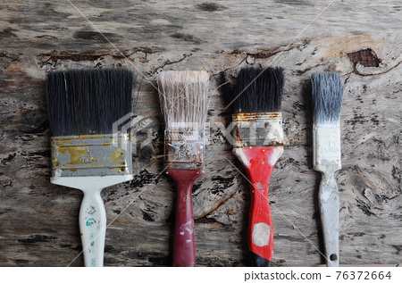 Old paint brush on old wood board. 76372664