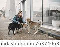 Man with a dogs in a city 76374068