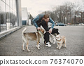 Man with a dogs in a city 76374070