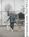 Man with a dogs in a city 76374072