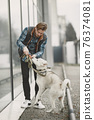 Man with a dog in a city 76374081