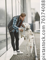 Man with a dog in a city 76374088