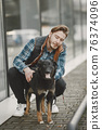 Man with a dog in a city 76374096