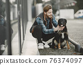 Man with a dog in a city 76374097